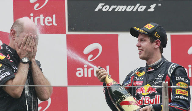 Red Bull driver Sebastian Vettel of Germany, right, sprays champaign to Red Bull's chief technical officer Adrian Newey during the award ceremony of the Indian Formula One Grand Prix at the Buddh