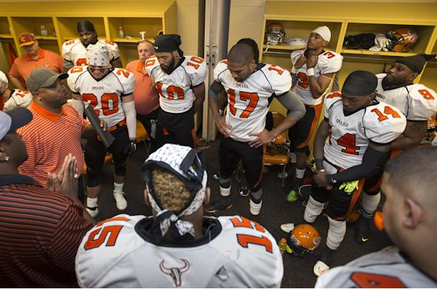 ADVANCE FOR WEEKEND EDITIONS, MAY 30-31 -  In this photo from May 16, 2015, Omaha Beef coach Cory Ross, at left holding folded papers, addresses his players in the locker room prior to playing the Sio