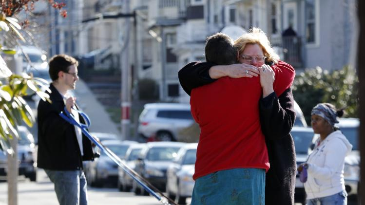 Neighbors hug outside the home of the Richard family in the Dorchester neighborhood of Boston, Tuesday, April 16, 2013.  Martin Richard, 8,  was killed in Mondays bombing at the finish line of the Boston Marathon. (AP Photo/Michael Dwyer)