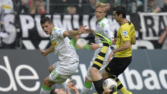 Moenchengladbach's Granit Xhaka of Switzerland, left, Dortmund's Robert Lewandowski of Poland, down, and Dortmund's Henrikh Mkhitaryan of Armenia, right, challenge for the ball during the German first division Bundesliga soccer match between Borussia Moenchengladbach and Borussia Dortmund in Moenchengladbach, Germany, Saturday, Oct. 5, 2013