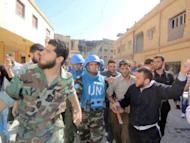 A handout picture released by Shaam News Network shows Abdul Razzaq Tlas (L) leader of the opposition Katibat al-Faruq, guides Moroccan UN observer, Colonel Ahmed Himmiche during the monitor's visit to the restive city of Homs