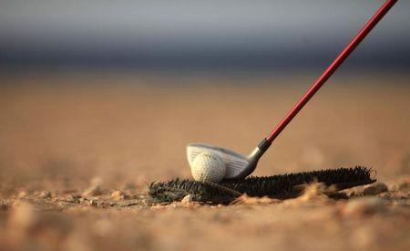 A golf club is positioned near a ball as a boy plays a game near the beach in Gargaresh area in Tripoli