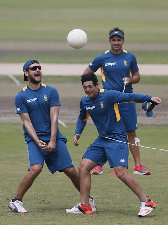 South Africa's Quinton de Kock, center, and his teammate Rilee Rossouw, left, play with a soccer ball during a practice session on the eve of the first Twenty20 match against Bangladesh in Dhaka, Bang