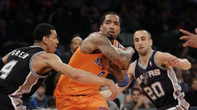 New York Knicks' J.R. Smith, center, drives through San Antonio Spurs' Danny Green, left, and Manu Ginobili during the second half of an NBA basketball game at Madison Square Garden, Sunday, Nov. 10, 2013, in New York. The Spurs won 120-89