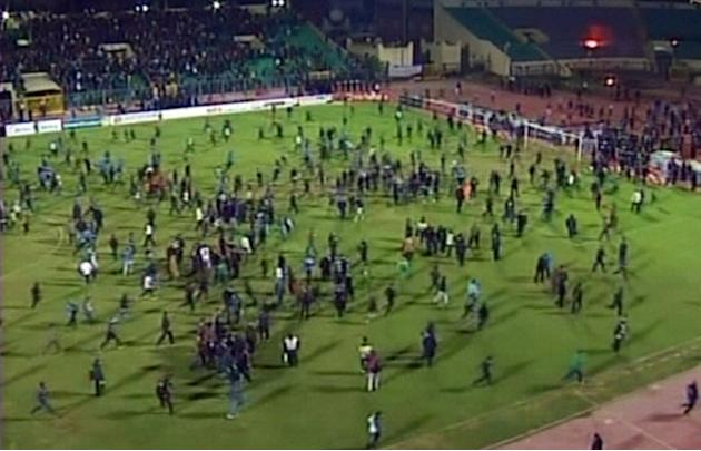A TV grab shows fans rushing onto the pitch during riots at the match between Al-Masry on February 1, 2012