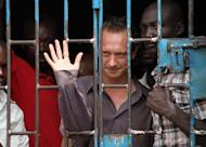 British theatre producer David Cecil waves from a cell at the Makindye Court on September 13, 2012 in Kampala. Cecil, who last year staged a play about homosexuality, which is illegal in Uganda, has been deported, the British High Commission says