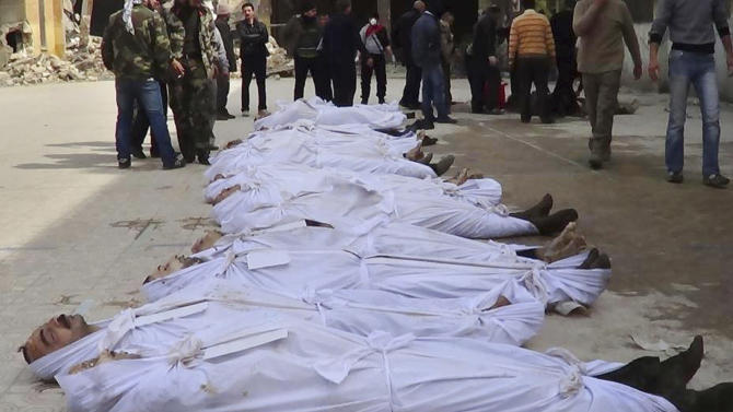 This citizen journalism image taken on, Sunday, March. 10, 2013 and provided by Aleppo Media Center AMC which has been authenticated based on its contents and other AP reporting, shows Syrians standing next to dead bodies that have been pulled from the river near Aleppo's Bustan al-Qasr neighborhood, Syria. Activists said the dead bodies of at least 20 men were pulled from a river that runs between regime- and rebel-controlled parts of the northern city. (AP Photo/Aleppo Media Center AMC)