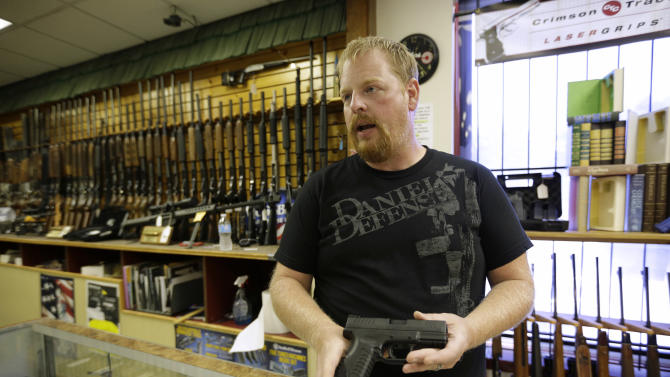 Eric Grabowski holds a hand gun in The Shooter Shop in West Allis, Wisconsin