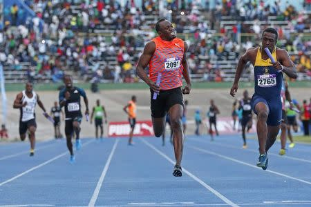 Usain Bolt runs next to Tyquendo Tracey while participating in his second race of the season during the Gibson Relays in Kingston