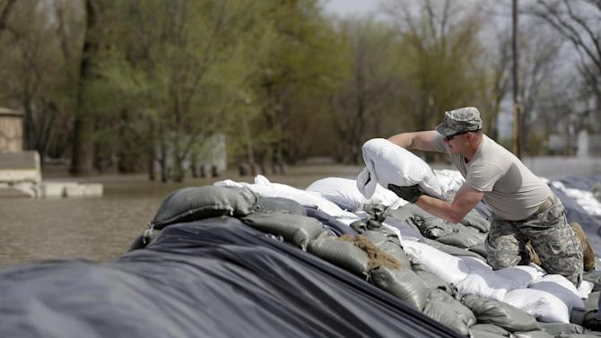 Sgt. First Class Nathan Jeffries of the Missouri National Guard 3175th MP Company from Warrenton, Mo., places sandbags on a trouble spot in a temporary levee Monday, April 22, 2013, in Clarksville, Mo. The swollen Mississippi River has strained a hastily erected makeshift floodwall in Clarksville, creating trouble spots that volunteers were scrambling to patch. (AP Photo/Jeff Roberson)