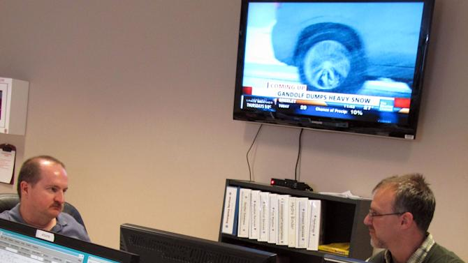 In a Jan. 10, 2013 photo, Richard Emanuel, left, and Rob Cox, National Weather Service forecasters in Cheyenne, Wyo., discuss the forecast as a storm dumped heavy snow on the western plains and Black Hills.This winter, the Weather Service is trying out simple, descriptive language to possibly replace its 14 watches, advisories and warnings for wintry weather _ from ice storms to blizzards, wind chill to lake-effect snow. (AP Photo/Mead Gruver)
