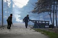 Soldiers pass burning houses amid ongoing violence in Sittwe, capital of Myanmar's western state of Rakhine, on June 12, 2012. A UN envoy has warned that communal violence in western Myanmar poses a threat to the country's shift towards democracy and said discrimination against the minority Muslim Rohingya was behind the unrest