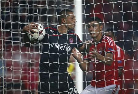 Benfica's Oscar Cardozo (R) tries to take the ball from Olympiakos' Jose Holebas after scoring a goal during their Champions League soccer match at Luz stadium in Lisbon October 23, 2013. REUTERS/Rafael Marchante