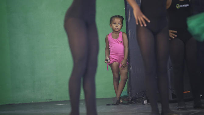 A girl watches dancers perform before members of London's Royal Opera House in the Vigario Geral slum of Rio de Janeiro, Brazil, Saturday, March 2, 2013. This past week Royal Ballet dancers shared their knowledge and advice with promising artists during an education symposium between the company and the cultural arts center Afro Reggae. (AP Photo/Silvia Izquierdo)