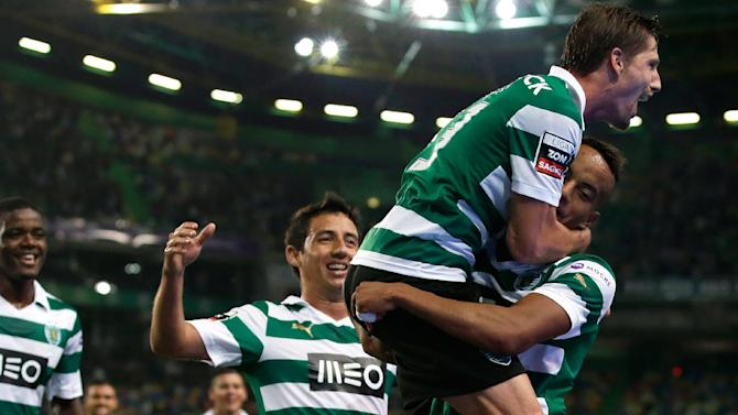 Sporting's Adrien Silva, top, right, jumps on teammate Andre Carrillo, from Peru, after he scored their second goal against Setubal  during their Portuguese league soccer match Saturday, Oct. 5 2013, at Sporting's Alvalade stadium in Lisbon. Sporting defeated Setubal 4-0 to take the lead of the championship
