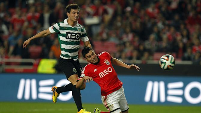 Benfica's Nico Gaitan, right, from Argentina, heads the ball to score the opening goal past Sporting's Cedric Soares during the Portuguese league soccer match between Benfica and Sporting at Benfica's Luz stadium, in Lisbon, Tuesday, Feb. 11, 2014