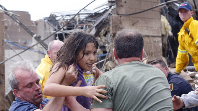 CORRECTS TORNADO MEASUREMENT TO NUMBER REPORTED BY THE NATIONAL WEATHER SERVICE - A child is pulled from the rubble of the Plaza Towers Elementary School in Moore, Okla., and passed along to rescuers Monday, May 20, 2013. A tornado as much as half a mile wide with winds up to 200 mph roared through the Oklahoma City suburbs Monday, flattening entire neighborhoods, setting buildings on fire and landing a direct blow on an elementary school. (AP Photo Sue Ogrocki)