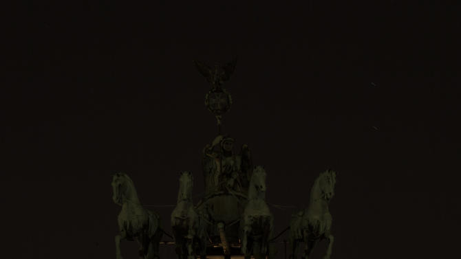 The normally illuminated Quadriga at top of the Brandenburger Gate is seen in darkness during Earth Hour in Berlin, Saturday, March 23, 2013. Earth Hour was marked worldwide at 8.30 p.m. local time and is a global call to turn off lights for 60 minutes in a bid to highlight the global climate change.(AP Photo/Markus Schreiber)