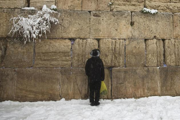 A man prays in the snow at the Western Wall, Judaism's holiest prayer site, in Jerusalem's Old City