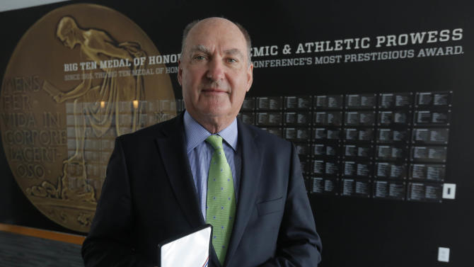 This Friday, March 7, 2014 photo shows Big Ten commissioner Jim Delany holding the Big Ten Medal of Honor that is exhibited in the The Big Ten Experience at the Big Ten conference's sparkling new headquarters in Rosemont, Ill. This year marks the 100th anniversary of the Big Ten Medal of Honor given to one male and female from each school based on their accomplishments on the field and in the classroom, and they are recognized here. The Big Ten Experience is not quite a hall of fame. It is an ode to the conference. Fans will be able to relive some of their favorite moments through a series of interactive exhibits touting its successes on the field and away from it when the museum opens in the spring or summer