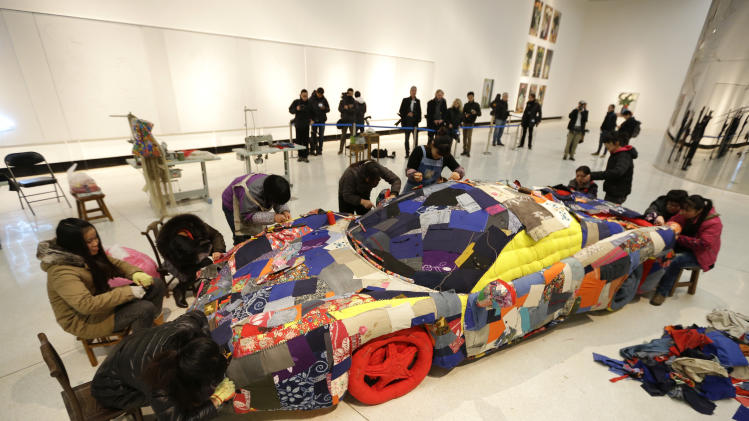 Women sew an art work based on a sports car model on the outskirts of Beijing