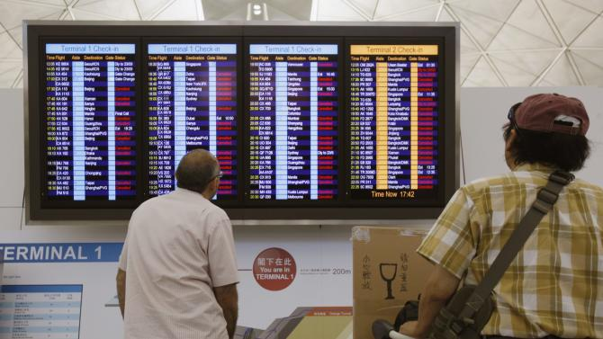 Pssengers look at an information board showing flights cancelled in anticipation of typhoon Usagi, at Hong Kong Airport