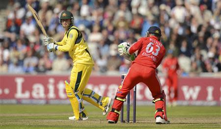 Australia's Clarke hits out watched by England's Buttler during the second one-day international at Old Trafford cricket ground in Manchester