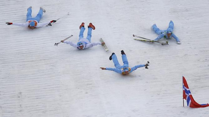 Norway's team members slide after the flower ceremony for the Nordic Combined team Gundersen event of the Sochi 2014 Winter Olympic Games