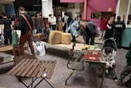 """People check second-hand furniture during the opening of the """"Riquet Bric-a-Brac"""" junk shop in Paris on September 1. French living standards dropped in 2010 as the eurozone debt crisis hit, with the poverty rate climbing to its highest in 13 years, data from the national statistics office showed"""