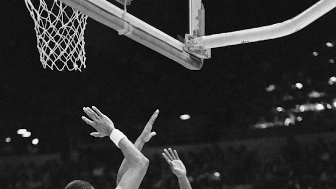 "FILE - In this June 4, 1982, file photo, Philadelphia 76ers' Darryl Dawkins, right, tries rto get past the defense ofliterally is swamped by the defense of the Loa Angeles Lakers Kareem Abdul-Jabbar (33) and Earvin Magic Johnson during second half action in Game 4 of the NBA Championship in Los Angeles. Darryl Dawkins, whose backboard-shattering dunks earned him the moniker ""Chocolate Thunder"" and helped pave the way for breakaway rims, has died. He was 58. The Lehigh County, Pennsylvania coroner's office said Dawkins died Thursday morning, Aug. 27, 2015,  at a hospital. (AP Photo/Doug Pizac, File)"