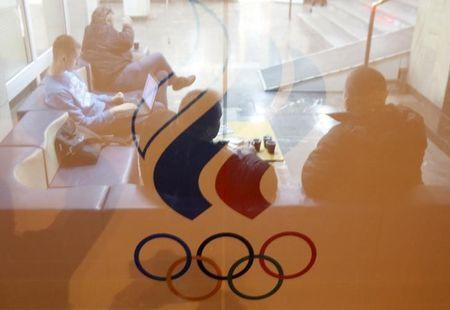 People are seen through a glass as they gather inside the headquarters of the Russian Olympic Committee in Moscow