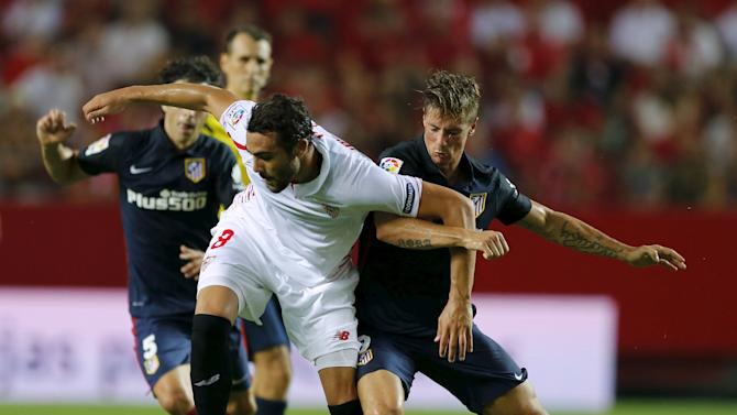 Sevilla's Vicente Iborra and Atletico MadridÕs Fernando Torres battle for the ball during their soccer match in Seville