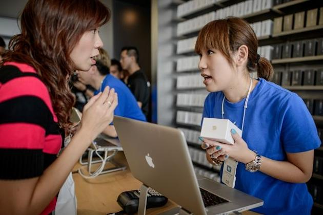 A woman (L) buys an iPhone 5 at the Hong Kong Apple store on September 21, 2012
