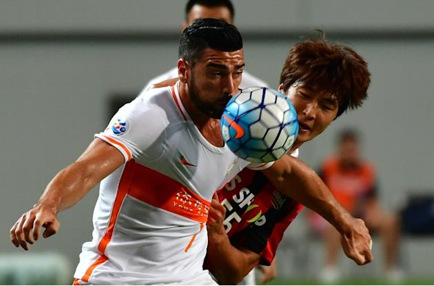 Shandong Luneng's Graziano Pelle (L) fights for the ball with FC Seoul player Kwak Tae-Hwi during an AFC Champions League match in Seoul, on August 24, 2016