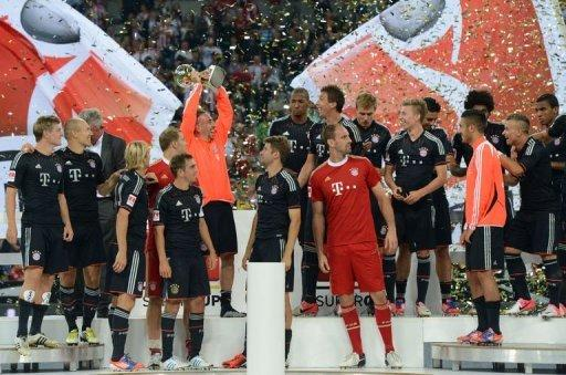Bayern Munich's French midfielder Franck Ribery (C) holds the trophy as he celebrates with teammates
