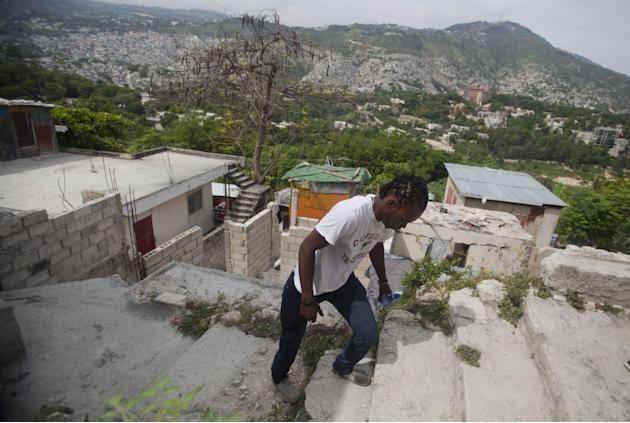 In this May 17, 2015 photo, Joseph Marc Carel, 24, motorbike taxi driver walks to get his motorbike in Port-au-Prince, Haiti. Cheap motorbikes such as the one that transformed this 24-year-old into an
