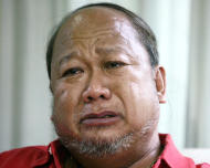 In this photo taken Aug. 4, 2011, Rudy Abad is overcame with emotion at his home in Tagaytay City, south of Manila, Philippines, as he narrated the last minutes of his wife Marie Rose Abad who died during the Sept. 11 2001 World Trade Center terrorist attacks in New York City. Unlike many victims of the 2001 attacks who are remembered mostly by their family and friends, Marie Rose Abad's legacy lives on half-way around the world in a once-notorious Manila slum now turned into a tidy village that carries her name. (AP Photo/Pat Roque)