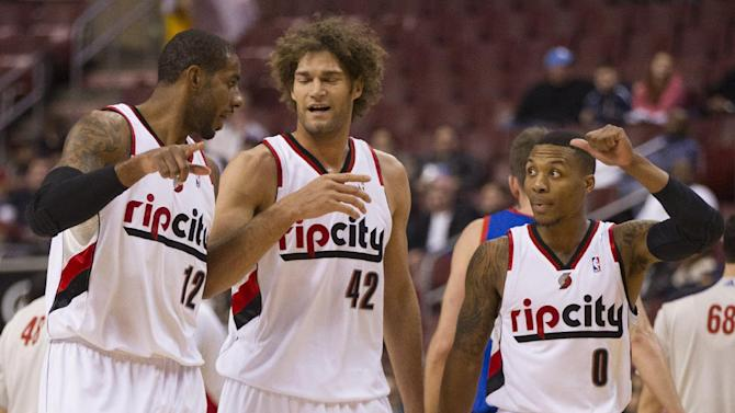 Portland Trail Blazers' LaMarcus Aldridge, left, talks with Robin Lopez, center, and Damian Lillard, right as they head back to the bench during the first half of an NBA basketball game against the Philadelphia 76ers, Saturday, Dec. 14, 2013, in Philadelphia. The Trail Blazers won 139-105