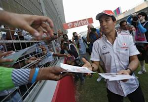 McLaren Formula One driver Sergio Perez of Mexico distributes his autographs to fans at the Buddh International Circuit in Greater Noida on the outskirts of New Delhi October 24, 2013.