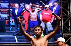 Manny Pacquiao shows off his candy snack at Friday's weigh-in. (AFP)