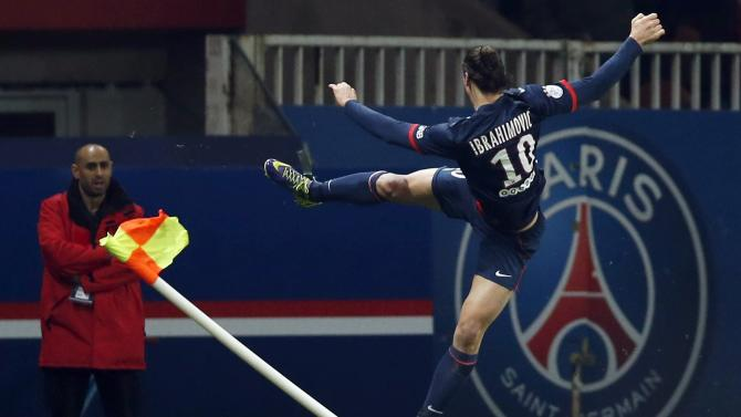 Paris St Germain's Zlatan Ibrahimovic jumps and kicks a corner flag as he celebrates scoring against FC Nantes during their French Ligue 1 soccer match at the Parc des Princes Stadium in Paris
