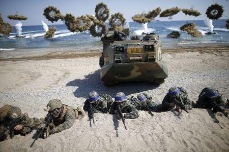 South Korean and U.S. Marines take positions as amphibious assault vehicles of the South Korean Marine Corps fire smoke bombs during a U.S.-South...