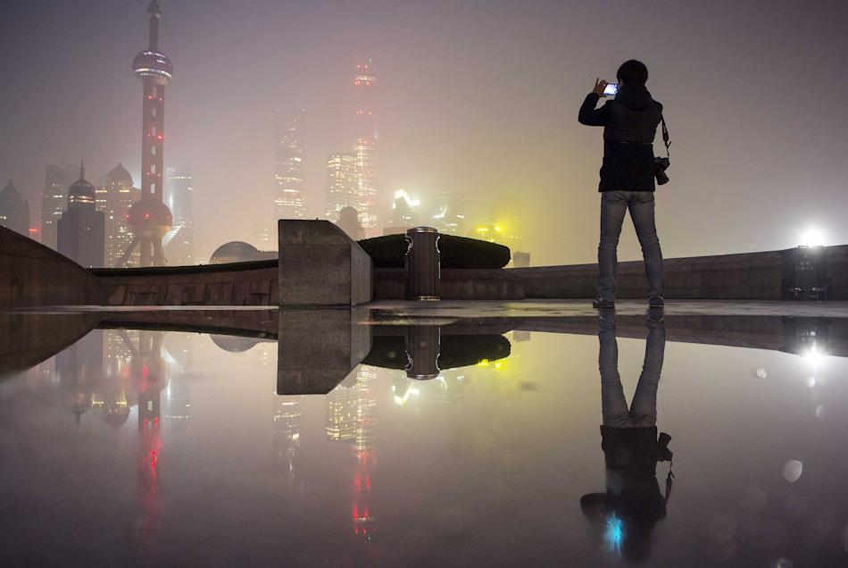 A man uses his mobile phone to take pictures of the financial area of Pudong New District (rear) on a smoggy day in Shanghai