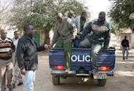 Zambian miners arrested over the death of a Chinese manager in a wage riot at a Chinese-owned coal mine, are escorted by Zambian police into a holding cell at Choma Magistrate Court in Sinazongwe on August 8, 2012. Zambia arrested 12 people over the death of the Chinese manager at the coal mine known for sometimes violent tensions with workers
