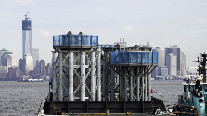 A barge loaded with sections of spire for One World Trade Center, left, is guided by tugboat across New York Harbor, Tuesday, Dec. 11, 2012 in New York. (AP Photo/Mark Lennihan)