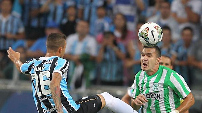 Luan of Brazil's Gremio, left, fights for the ball with Alejandro Bernal of Colombia's Atletico Nacional during a Copa Libertadores soccer game in Porto Alegre, Brazil, Tuesday, Feb.25, 2014