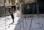 A Syrian rebel aims his weapon as he tries to dodge pro-government sniper fire while running across a street in the Salaheddin district of the northern city of Aleppo on August 13, 2012. Syrian rebels claimed they downed a fighter jet in what would be a major coup for the opposition but the regime seized the upper hand in Aleppo as it advanced into a new rebel-held district