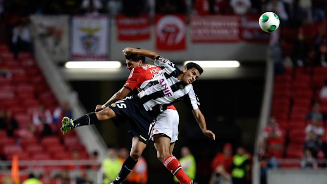 Benfica's Enzo Perez, left, fights for the ball with Nacional's Jota during their Portuguese league soccer match at Benfica's Luz stadium in Lisbon, Sunday, Oct. 27 2013