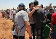Residents of the Libyan city of Benghazi mourn on June 9, 2013 as they bury the bodies of demonstrators killed during clashes between former rebels and anti-militia protestors. Clashes between Libyan elite forces and gunmen killed six soldiers in Benghazi on Saturday, the army said, in the latest bout of unrest as the government struggles to control rebels from the 2011 uprising