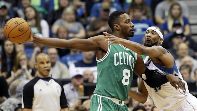 Boston Celtics' Jeff Green, left, keeps the ball at arm's length as Minnesota Timberwolves' Corey Brewer tries to reach it in the first quarter of an NBA basketball game on Saturday, Nov. 16, 2013, Minneapolis